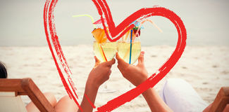 Composite image of couple clinking glasses of cocktail on beach. Couple clinking glasses of cocktail on beach against print royalty free stock photo