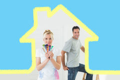 Composite image of couple with color swatches and ladder in a new house Stock Image