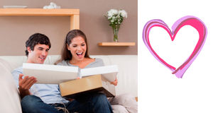 Composite image of couple on the couch opening parcel Stock Images