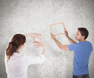 Composite image of couple deciding to hang picture Royalty Free Stock Image
