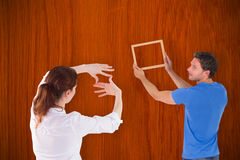 Composite image of couple deciding to hang picture Royalty Free Stock Photo