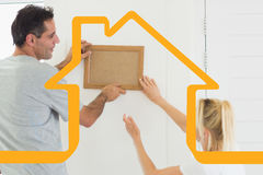Composite image of couple decorating their new house Stock Photo