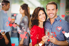 Composite image of couple drinking champagne and valentines hearts 3d Royalty Free Stock Photos