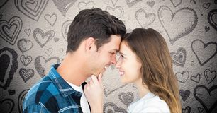 Composite image of couple embracing against grey background with valentines hearts Stock Photo