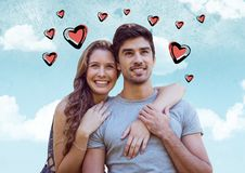 Composite image of couple embracing against sky with pink valentines hearts Stock Photos