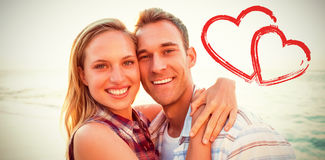 Composite image of couple embracing at beach Stock Image