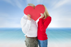 Composite image of couple embracing and holding heart over faces Royalty Free Stock Photos