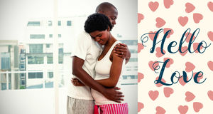 Composite image of couple embracing and valentines words. Valentines words against pregnant couple cuddling at home Stock Photo