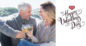 Composite image of couple enjoying white wine on picnic at the beach Stock Image