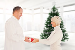 Composite image of couple exchanging gift Stock Photos