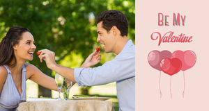 Composite image of couple feeding strawberries to each other at outdoor café Royalty Free Stock Photo