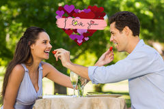 Composite image of couple feeding strawberries to each other at outdoor café Royalty Free Stock Photos
