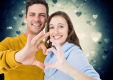 Composite image of couple forming heart shape with hands. Composite image of happy couple forming heart shape with hands Royalty Free Stock Photo