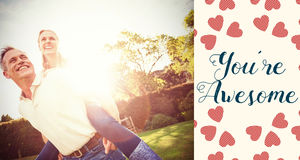 Composite image of couple in garden and valentines words. Valentines words against husband giving piggy back to wife Stock Photo