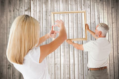 Composite image of couple hanging a frame together Stock Image