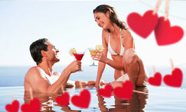 Composite image of couple having cocktails in the pool Royalty Free Stock Photos