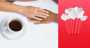 Composite image of couple having coffee together holding hands. Couple having coffee together holding hands against hearts royalty free stock photos