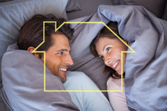 Composite image of couple having fun wrapped in their blanket Stock Images