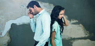 Composite image of couple with head in hands standing back to back. Couple with head in hands standing back to back against rusty weathered wall Royalty Free Stock Images