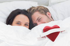Composite image of couple hiding under the duvet Royalty Free Stock Image