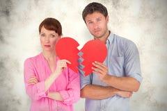 A Composite image of couple holding a broken heart Stock Photos