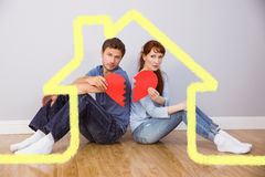 Composite image of couple holding a broken heart Royalty Free Stock Image