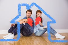 Composite image of couple holding a broken heart Stock Images