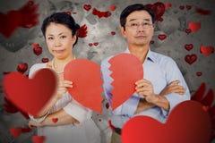 Composite image of couple holding broken heart. Couple holding broken heart against love heart pattern Stock Photos