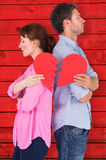 Composite image of couple holding a broken heart Stock Photo