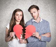 Composite image of couple holding broken heart Stock Image
