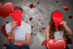 Composite image of couple holding broken heart 3D. Couple holding broken heart against love heart pattern 3D Royalty Free Stock Image