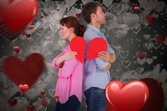 Composite image of couple holding a broken heart 3D. Couple holding a broken heart against love heart pattern 3D Royalty Free Stock Photo