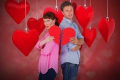 Composite image of couple holding a broken heart 3d. Couple holding a broken heart against valentines heart design 3d Royalty Free Stock Photos