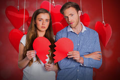 Composite image of couple holding broken heart 3d. Couple holding broken heart against valentines heart design 3d Royalty Free Stock Image