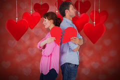 Composite image of couple holding a broken heart 3d. Couple holding a broken heart against valentines heart design 3d Royalty Free Stock Images
