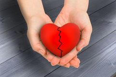 Composite image of couple holding broken heart in hands Royalty Free Stock Photo