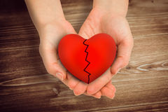 Composite image of couple holding broken heart in hands Stock Images