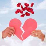 Composite image of couple holding a broken paper heart Stock Photography