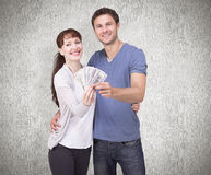 Composite image of couple holding fan of cash Stock Images