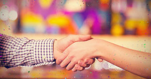 Composite image of couple holding hands in bar. Couple holding hands in bar against flying colours Stock Photos