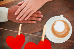 Composite image of couple holding hands beside cappuccino Stock Photos