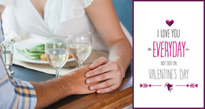 Composite image of couple holding hands at dinner. Couple holding hands at dinner against valentines day greeting royalty free stock photography