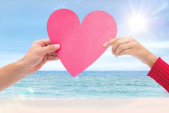 Composite image of couple holding a heart Royalty Free Stock Images