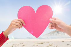 Composite image of couple holding a heart Stock Photography