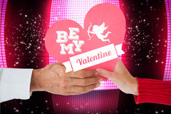 Composite image of couple holding heart. Couple holding heart against glittering screen on black background stock image