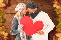 Composite image of couple holding heart while looking at each other Royalty Free Stock Photos