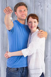 Composite image of couple holding keys to home Royalty Free Stock Photo