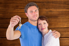 Composite image of couple holding keys to home Stock Images