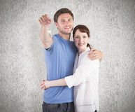 Composite image of couple holding keys to home Stock Image