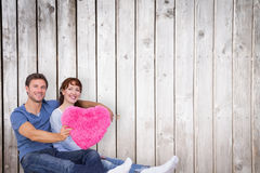 Composite image of couple holding a large heart Royalty Free Stock Photo